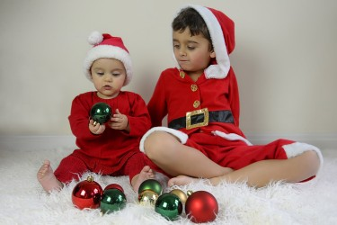 Baby and brother looking at Christmas baubles