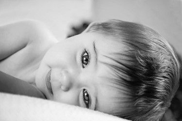 Close up face of eight month old baby laying on side looking at camera,