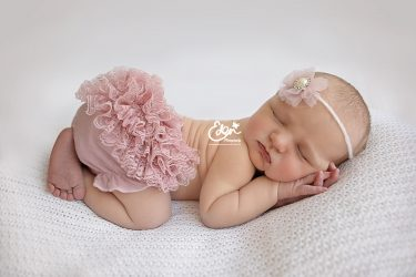 Baby laying in tushie pose