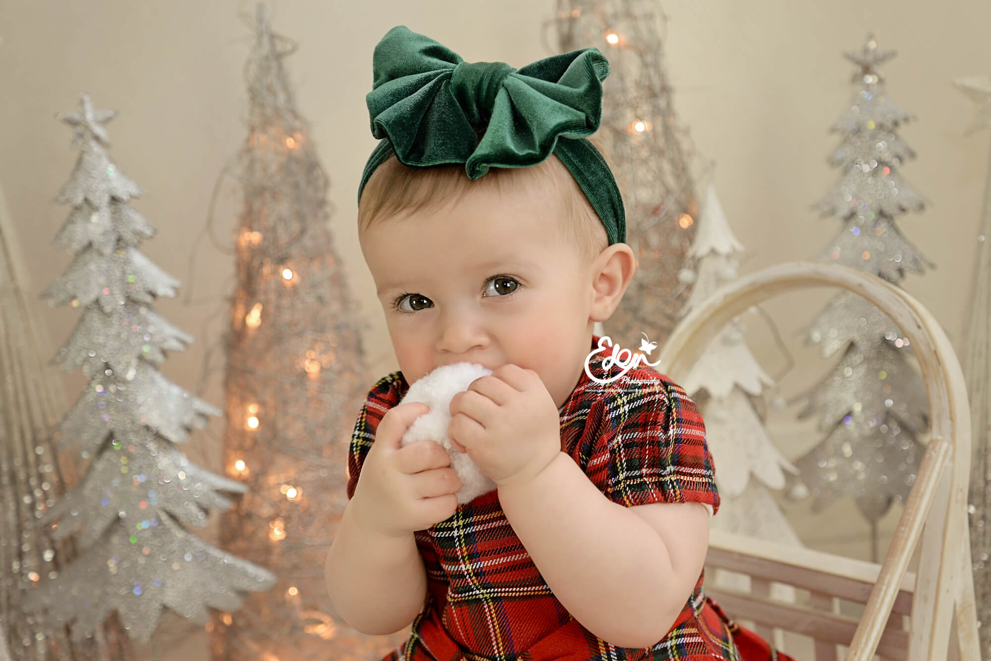 Baby girl sitting in front of Christmas Decor.