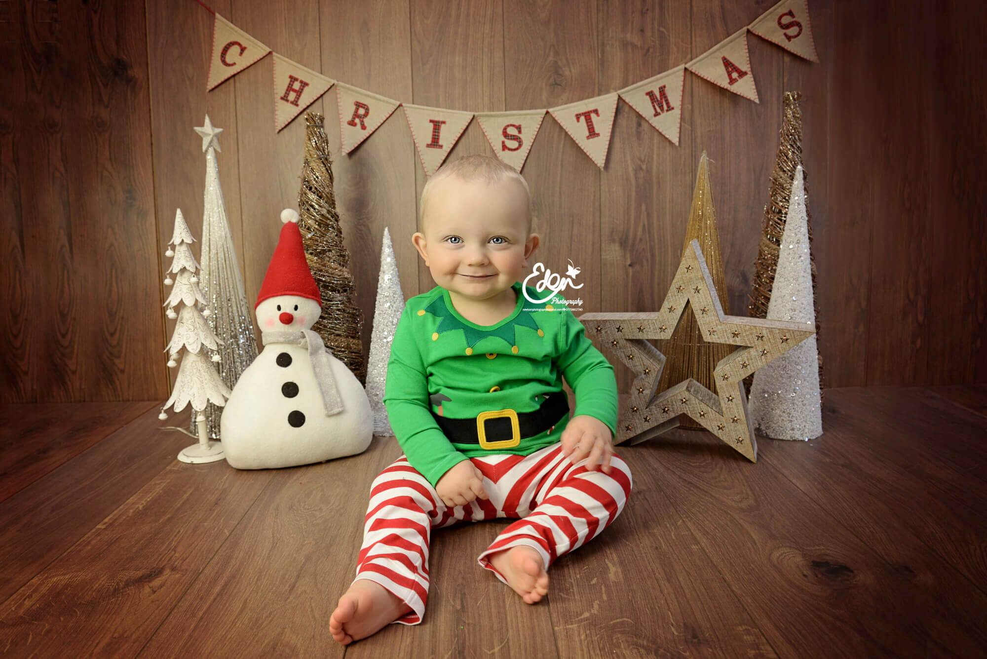Baby boy sitting in front of Christmas Decor.